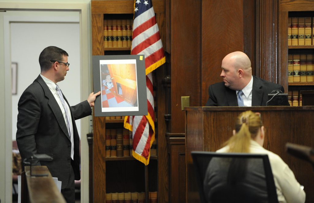 "From left, defense attorney Patrick Noonan, shows East Bridgewater police officer Peter Belmore, a photograph of the couples home a door panel leading into the laundry room that seemed to be kicked out. The trial for a former Boston firefighter accused of assaulting his wife began Tuesday in Brockton Superior Court.<br /> Richard R. Parker, who worked for the Boston Fire Department for nearly 26 years and was also a 9/11 responder, faces a charge of assault to murder amid others against his wife, Kimberly Boleza Parker, from an alleged incident in 2011. Parker died March 10, 2013 of causes that have not yet been determined.<br /> On Dec. 18, 2011, at 5 a.m., police responded to a 911 call placed from their Satucket Avenue home reporting that Parker was ""threatening his wife with a knife,"" police logs show.<br /> In a written testimony following the incident, Kimberly Parker described a violent scene in which Parker was throwing knives at her while she stood pinned against a bedroom wall, according to court records.<br /> She was able to escape, she wrote, after one knife took a bad bounce and landed out of sight.<br /> Parker, 58, of 3 Satucket Ave., was indicted in 2012 following his wife's testimony in front of a grand jury. He is charged with kidnapping; assault to murder; assault with a dangerous weapon, a knife; threat to commit a crime and intimidation of a witness.<br /> Police, on two prior occasions before 2011, responded to the home for abuse reports.<br /> Kimberly Parker died March 10, 2013 at age 45 in her East Bridgewater home of causes that have not yet been determined.<br /> (Marc Vasconcellos/The Enterprise)"