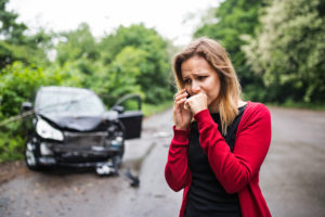 A Young Woman With Smartphone By The Damaged Car After A Car Acc